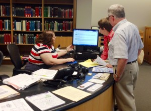 Librarian Delia Bourne helps people at the Genealogy Center desk.